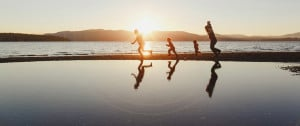 a family running on the beach in the setting sun, representing potential customers for community solar from 3Degrees