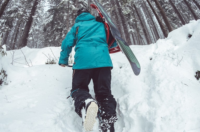 Snowboarder treks up the snow