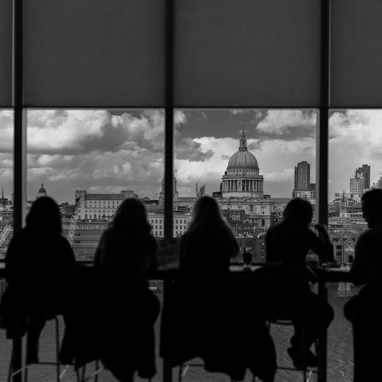 people sitting in an office building, silhouetted against backdrop of a city